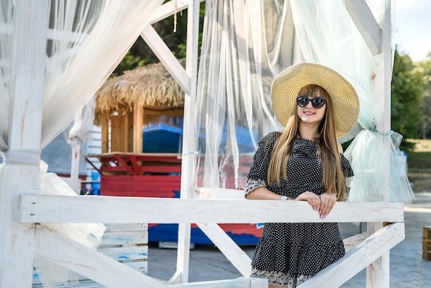 ファッションの女の子は夏の時間に自然で休む