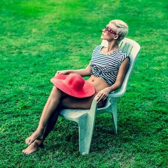 Мода девушка сидит на стуле в парке