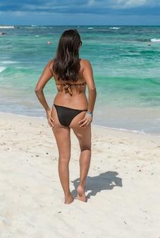 美しい午後に青い海を見て砂の上に立っているファッションの女の子。彼女の背中に水着を着ている女性。海を見て魅力的な女性の裏。