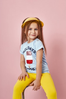 Fashion girl in stylish clothes on colored wall. autumn bright clothes on children
