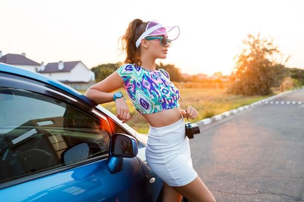 Ragazza di modo in cappuccio trasparente alla moda in posa vicino all'auto durante il viaggio