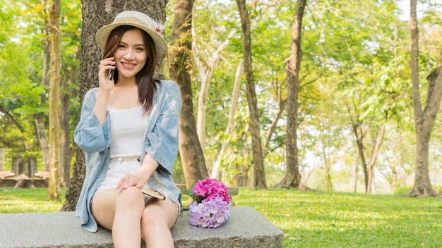Fashion girl use phone in garden park.