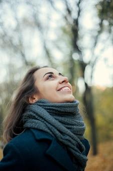 秋の森でトレンチ コートを着たファッションの女の子