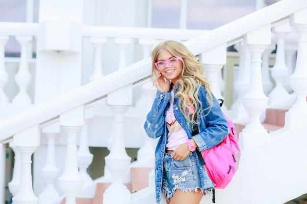 春のストリート、ピンクのバッグとデニムの服の夏のファッションの女の子