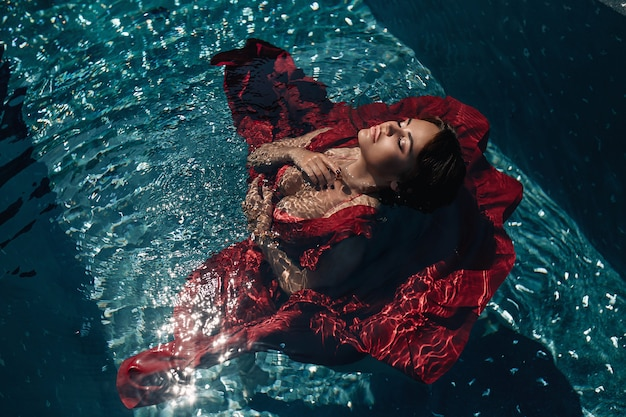 Fashion : girl with bright make up in a red dress lying  water the pool. young woman with closed eyes posing in water