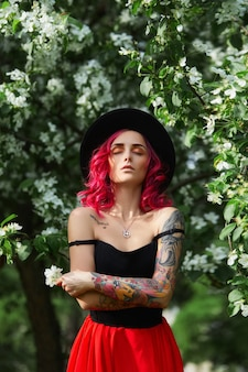 Fashion girl with bright red dyed hair in apple and lilac flowers. creative color bright pink, colorist. woman walks in a park enjoys the spring