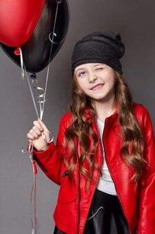 컬러 풍선 윙크와 함께 패션 소녀입니다. 어두운 배경에 스튜디오 사진