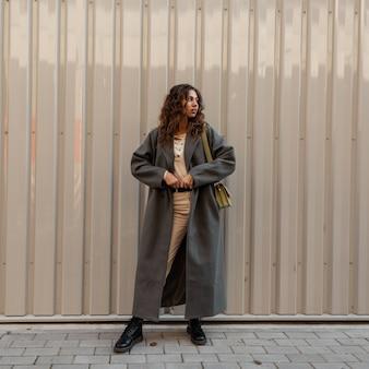 핸드백이 달린 빈티지 녹색 긴 코트에 곱슬머리를 한 패션 소녀는 금속 벽 근처에 서 있습니다. 어반 페미닌한 스타일과 아름다움