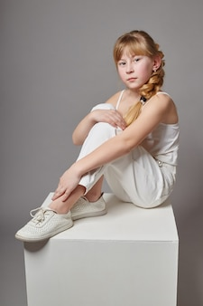 Fashion girl with long hair in casual clothes sitting on a white cube and posing. beautiful young child. russia, sverdlovsk, february 4, 2018