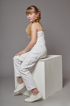 Fashion girl with long hair in casual clothes sitting on a white cube and posing