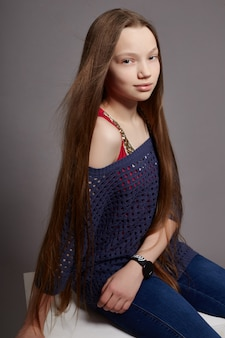 Fashion girl with long hair casual clothes sitting