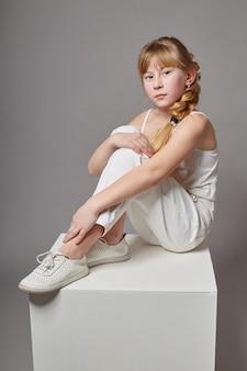 화이트 큐브에 앉아서 포즈를 취하는 캐주얼 옷에 긴 머리를 가진 패션 소녀. 아름다운 어린 아이. 러시아, 스 베르들 롭 스크, 2018 년 2 월 4 일