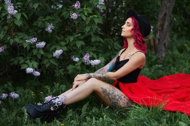 빨간 머리와 큰 모자 직업, 여름에 라일락 색상에서 봄 초상화 패션 소녀. 아름 다운 빨간 분홍색 드레스, 여자의 몸에 문신. 밝은 메이크업, 전문적인 헤어 컬러링