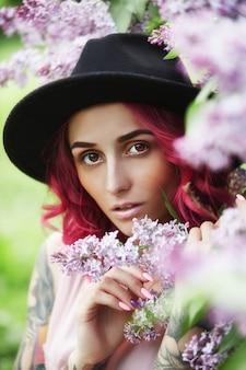 빨간 머리 직업, 여름에 라일락 색상에서 봄 초상화와 패션 여자. 아름 다운 빨간 분홍색 드레스, 여자의 몸에 문신. 밝은 메이크업, 전문적인 헤어 컬러링