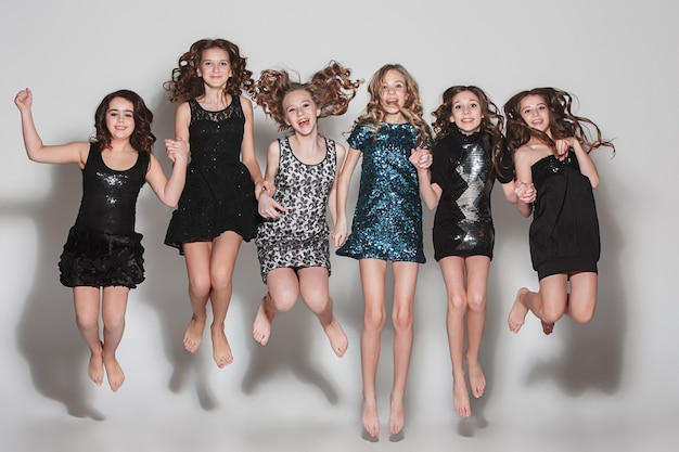 Fashion girls jumping together and looking at camera over gray
