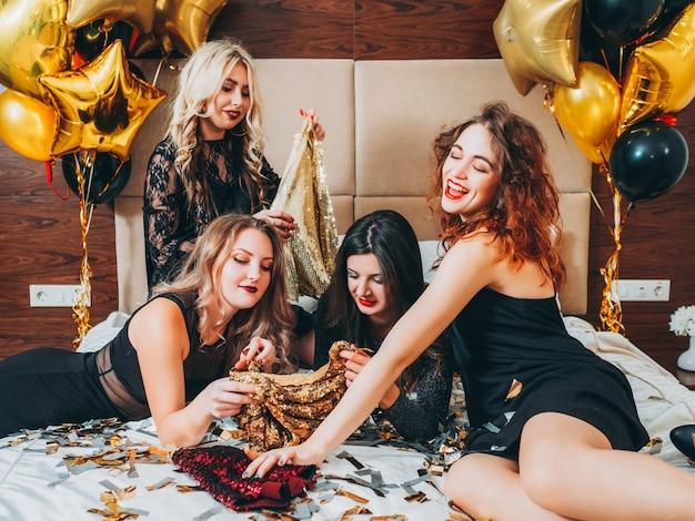 ファッションの女の子のリラクゼーションタイム。グラマーな外観とライフスタイル。スパンコールの衣装を選んでベッドに横たわっている黒い服の娘たち。トレンド。