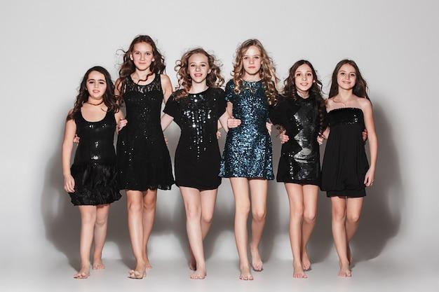Модные девушки стояли вместе и смотрели на камеру над серой студией