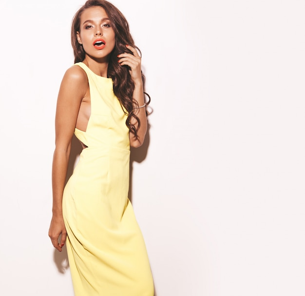 Fashion glamor stylish beautiful young woman model with red lips in summer bright yellow dress isolated on white