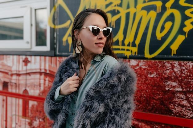 街でポーズをとるゴールドジュエリーとトレンディな毛皮のコートとメガネのファッショングラマー女性