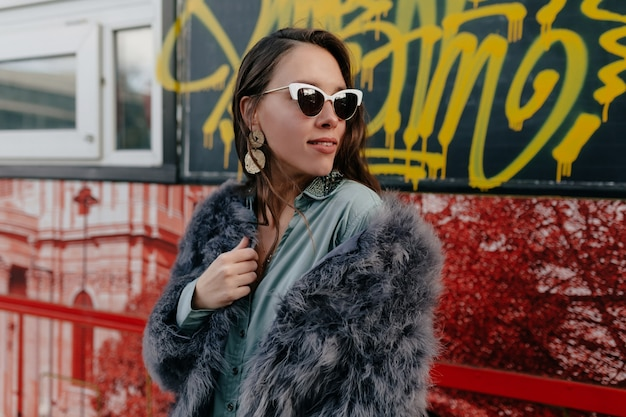 Fashion glamour woman in trendy fur coat and glasses with gold jewelry posing on city