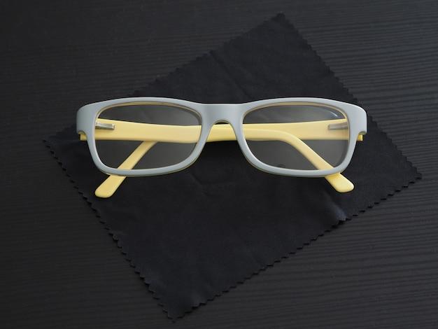 Модные очки желто-серого цвета в пластиковой оправе лежат на пыльнике из микрофибры для очков.