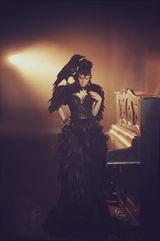 Fashion gothic portrait of a beautiful brunette with raven in a long black dress made of raven feathers. halloween