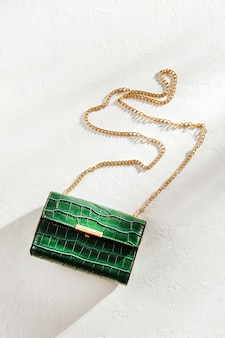 Fashion green handbag on white background flat lay top view
