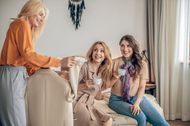 ファッション。新しいファッショナブルな服について話し合い、興奮している女性のグループ