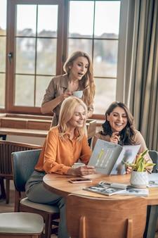 ファッション。一緒に時間を過ごし、ファッション雑誌を見て女性のグループ