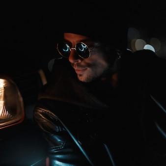 어둠 속에서 검은 가죽 재킷을 입은 세련된 선글라스를 쓴 패션 남자. 어반 남성 캐주얼 스타일