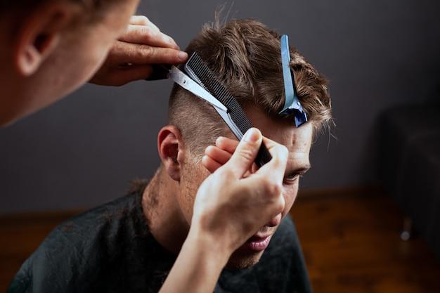 Модная стрижка, молодой парень стрижет волосы в парикмахерской. парикмахерская.