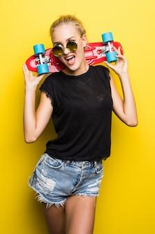 Moda ragazza cool hipster sorridente felice in occhiali da sole e vestiti colorati con skateboard divertendosi all'aperto sullo sfondo arancione