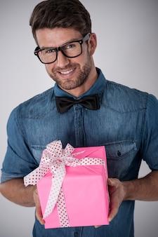 ピンクの贈り物を持つファッション流行に敏感な男