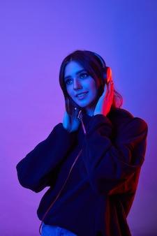 Мода битник женщина носить наушники, слушая музыку на цветном неоновом фоне в студии.