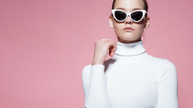Фасонируйте изображение шикарной элегантной женщины в белизне связало гольф и солнечные очки представляя над розовой стеной.