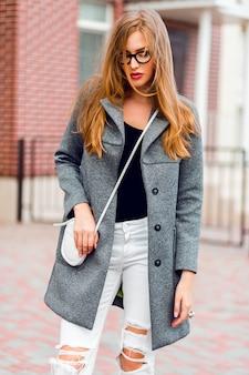 Фасонируйте изображение стильной белокурой женщины в сером пальто гуляя на улицу.