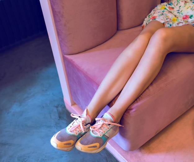 パステルカラーのスニーカーとバラのソファに座っているミニドレス、ネオンムード、柔らかな色を身に着けている女性の長いスリムな脚のファッションイメージ。