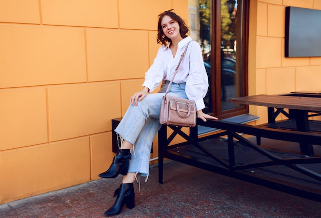 Fashion image of pretty brunette girl with short hairstyle in stylish casual white blouse and jeans. black leather boots on heels . girl sitting near modern cafe with yellow walls.