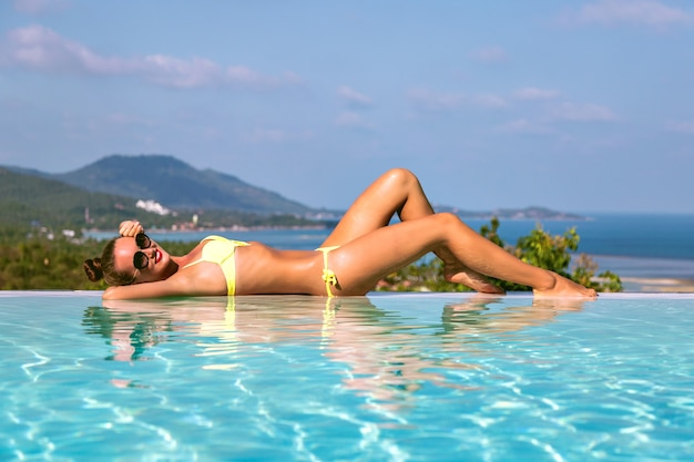 Fashion image of stunning sexy woman with slim fit body relaxing near infinity pool, at exotic tropical island, hot days, bikini, luxury living, travel vacation mood.