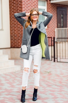Fashion image of stylish blond woman in grey coat walking on the street. full lenght.