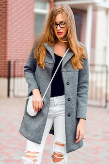 Fashion image of stylish blond woman in grey coat walking on the street.