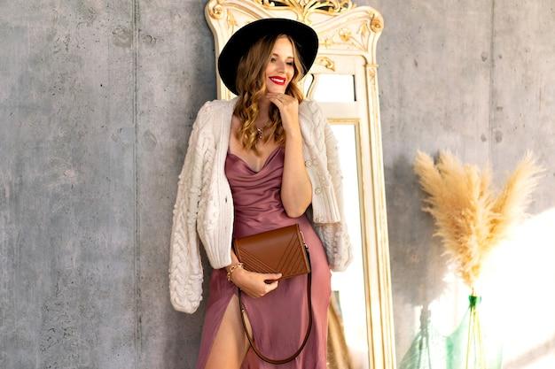 晴れた日に灰色の壁の近くでポーズをとって、シルクのドレス、暖かいニットのカーディガンと黒い帽子を身に着けている美しい魅力的な女性のファッション屋内肖像画
