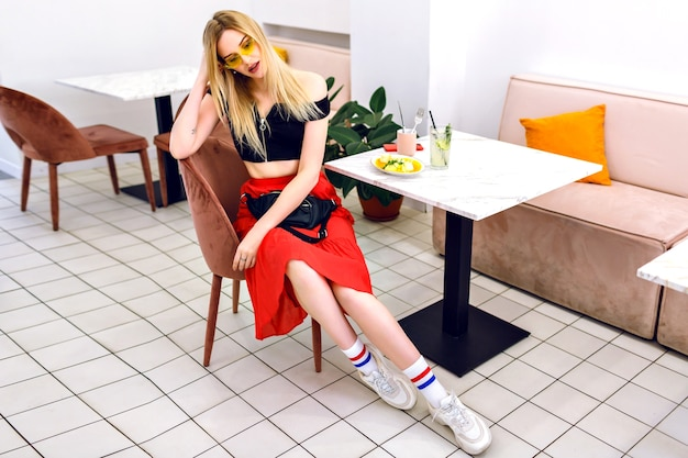 モダンな流行に敏感なカフェ、朝の朝食時にポーズをとって若いトレンディな流行に敏感な金髪女性のファッション屋内ポートレート。