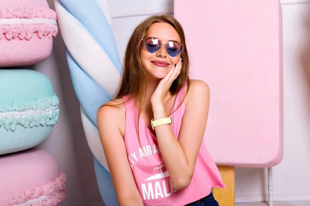 大きな偽のマカロンとキャンディーの近くでポーズをとる驚くべき美しい若い女性のファッション屋内流行の肖像画。顔の近くで手をつないでハートサングラスと幸せなブロンドの女の子。満足のいく笑顔