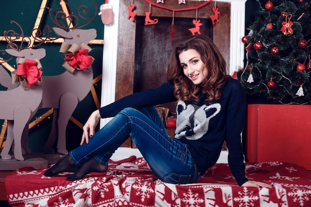 Fashion interior photo of beautiful young woman with dark hair and charming smile, posing beside christmas tree and chimney