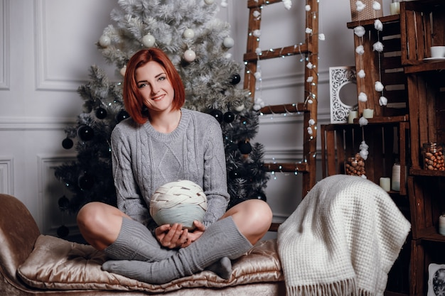 Модное интерьерное фото красивой молодой женщины с рыжими волосами и очаровательной улыбкой, носит уютный вязаный кардиган, позирует возле елки и дарит шоколадный торт со звездочками