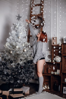 Мода интерьер фото красивой молодой женщины с рыжими волосами и очаровательной улыбкой, носит уютный вязаный кардиган