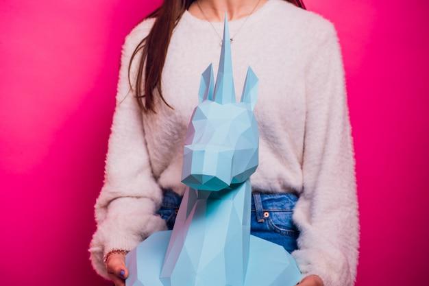 ファッションの子供。デザイナーコレクション。白い大きなユニコーン折り紙は紙を作った。美しいピンクのドレスの女の子。スタジオ撮影。