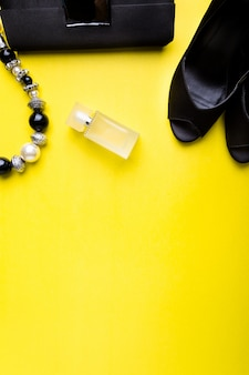 Fashion lady accessories set. black and yellow. minimal. black shoes, bracelet, perfume and bag on yellow . flat lay.