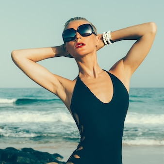 Fashion lady on the beach. stylish swimsuit and accessories